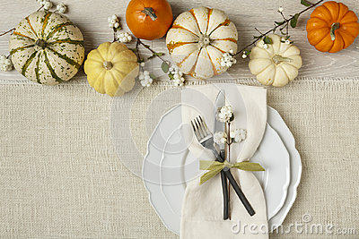 Festive fall autumn Thanksgiving table setting with natural botanical decorations and white fabric tablecloth background