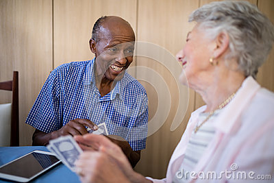 Smiling senior male and female friends playing cards
