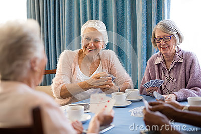 Smiling senior female friends playing cards
