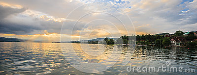 Panoramic summer view of boat cruise excursion landscape on Zurichsee with beautiful sunset shining light through clouds reflected