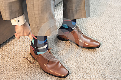 Man putting on brown dress shoes in formal wear with colorful socks