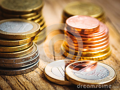 Stacked shiny white and golden Euro coins of different value on wood background, finances, investment, stock, savings concept