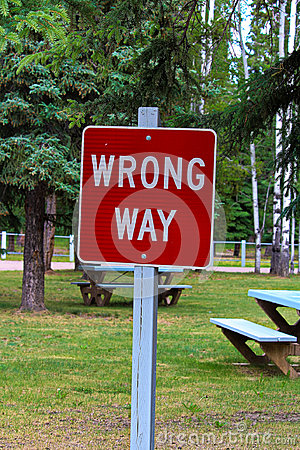 A red wrong way sign with picnic tables behind it