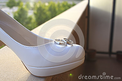 Two rings over a wedding shoe over