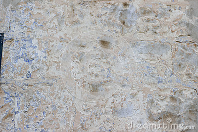 Stone wall with a multilayered old tumbling whitewash texture