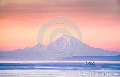 A ferry crossing the Puget Sound at sunrise with Mount Rainier i