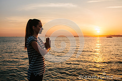 Young beautiful girl practicing yoga and meditation next to the sea at sunset. Sport. Yoga. Meditation. Recreation