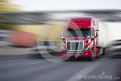 Bright red modern big rig semi truck with semi trailer move with