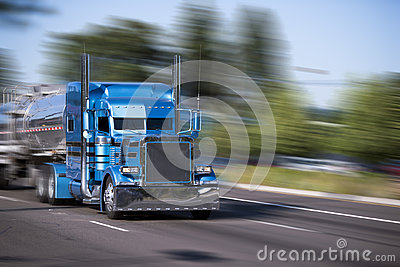Impressive customized blue big rig semi truck with tank trailers