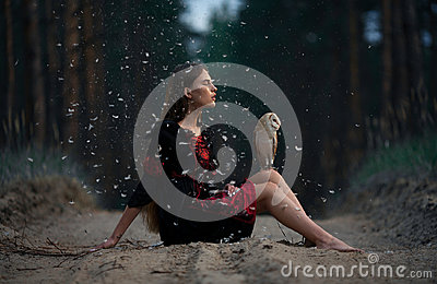 Girl sits on forest road with owl on her knees among flying fluff .