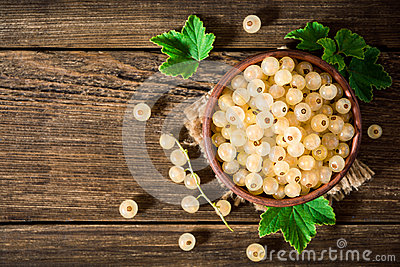 Fresh white currant in ceramic bowl on dark wooden background.