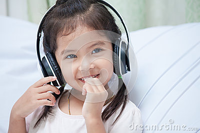 Cute asian child girl in headphones listening the music