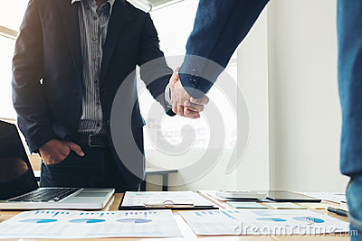 Two business men shaking hands during a meeting to sign agreement and become a business partner, enterprises, companies, confident