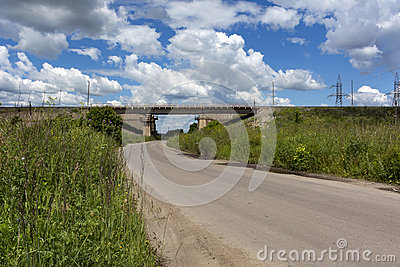 Asphalt road leads to the railway bridge, sky, clouds, grass