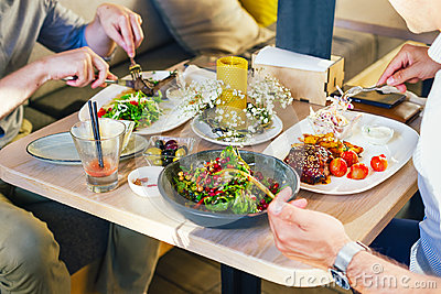 At the table, two men eat dinner, eat a steak, with a salad on a white plate, with a fork and knife in their hands.