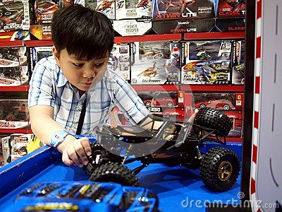 A young boy plays with radio controlled cars in a toy store.