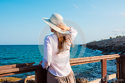 Young beautiful slender woman in sunhat with long hair in boho style clothes at the shore looking and the sea clear blue sky