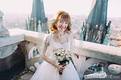 Elegant bride with bridal bouquet poses on the tower balcony of old gothic cathedral
