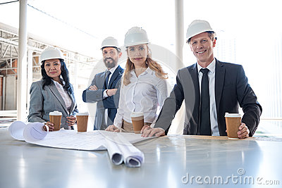 Multiethnic contractors in formal wear working with blueprints at construction area