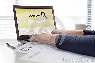 Man trying to find work with online job search engine on laptop. Jobseeker in home office. CV and application paper on table.