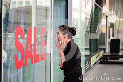 Beautiful caucasian woman excited when see the price tag on sale clothing fashion at the store