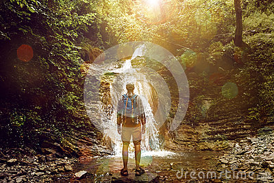 Tourist Man Reached Destination And Enjoys View Of Waterfall, Rear View, Contemplation Adventure Concept