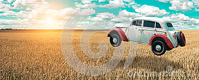 Flying car soars into the sky. Retro automobile hovers in the air above a golden wheat field on the background of blue sky.