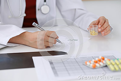 Female medicine doctor fills up  prescription form to patient closeup. Panacea and life save, prescribe treatment, lega