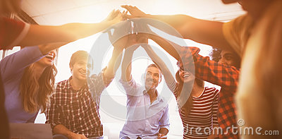 Cheerful business people giving high five while sitting creative office