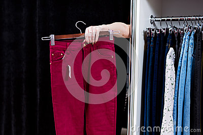 Woman trying on pants in a clothing store reaching out hand from a fitting room holding trousers