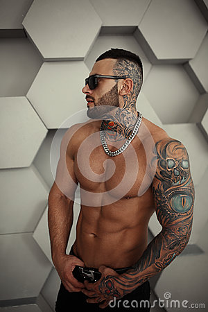 closeup topless portrait of Elegant handsome male model with fashion tattoo and a black beard standing and posing