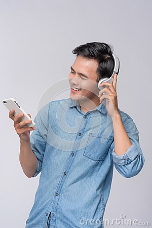 Handsome young man wearing headphones and holding mobile phone w
