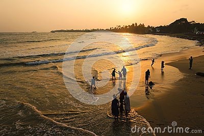 Matara, Sri Lanka, 04-15-2017: Golden sunset in the tropics on the ocean. Silhouette of people walking along the beach and water.