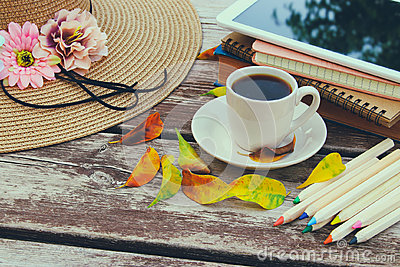 Digital tablet, books, colorfull pencils and cup of coffee on old wooden table outdoor in the park
