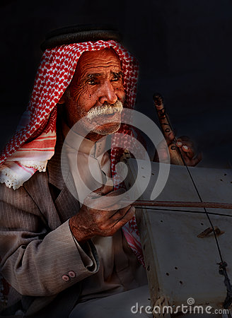 Little Petra, Jordan – June 20, 2017:Old Bedouin man or Arab man in traditional outfit, playing his musical instrument .