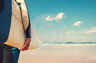Surf board in surfer`s hand close up image with oceans waves vie