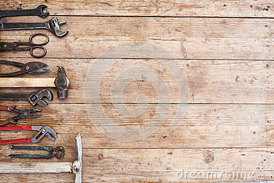 Composition of construction tools on an old battered wooden surface of tools: pliers, pipe wrench, screwdriver, hammer, metal shea