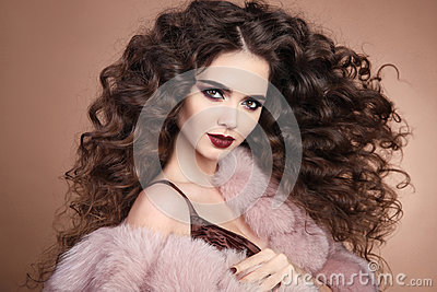 Hairstyle. Curly hair. Fashion brunette girl with long curly hai