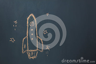 Flat lay Handmade drawing rocket ship launch / take off to the space with star on the blackboard by chalk board.