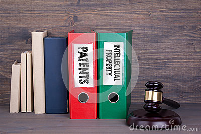 Patents and Intellectual Property. Wooden gavel and books in background. Law and justice concept