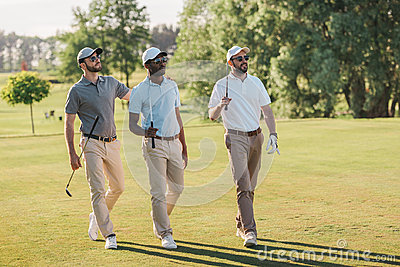 Smiling men in caps and sunglasses holding golf clubs and walking on lawn