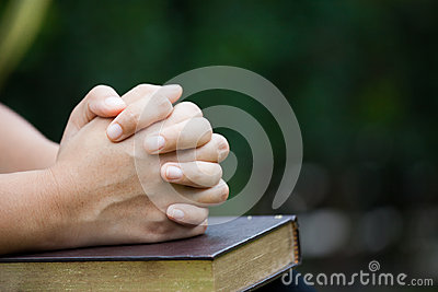 Woman hands folded in prayer on a Holy Bible for faith concept