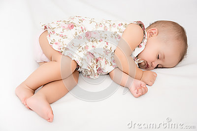 Baby lying on a bed while sleeping in a bright room