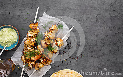 Barbecued chicken breast skewers with flat bread and avocado sau