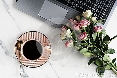 Flat lay, top view office table feminine desk. workspace with laptop, cup of cofee and bouquet pink roses.Mother`s day, birthday