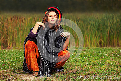 Young fashion hipster woman in rasta poncho sitting on the ground