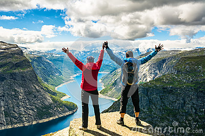 Couple standing against amazing nature view on the way to Trolltunga. Location: Scandinavian Mountains, Norway, Stavanger. Artist