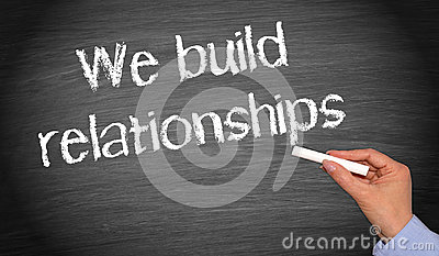 We build relationships - female hand with chalk writing text