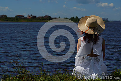 Woman in white dress sits on riverside, back view