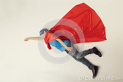 Superhero kid flying. Super hero boy in red cape and blue mask. copyspace, toned